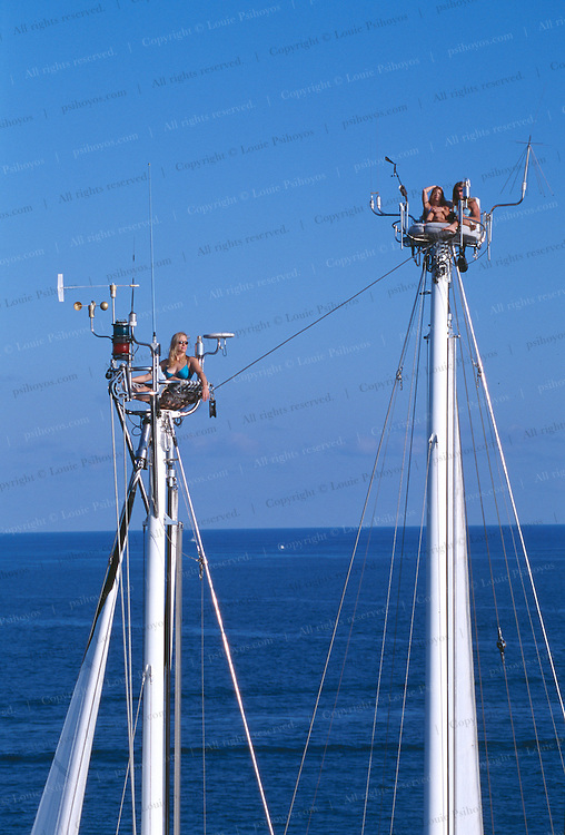 Guests ride twin elevators up to sky chairs atop the masts of the schooner Starship Andromeda outside Miami Beach, Florida.