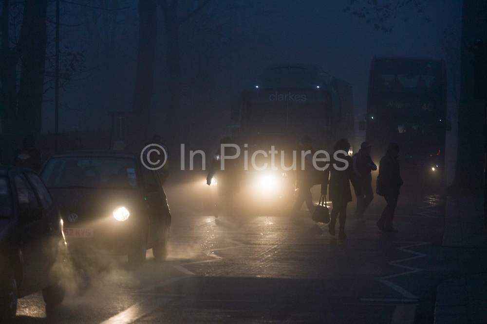 Pedestrians cross in front of commuter traffic at dawn on a foggy morning in south London. Crossing over the nearby Denmark Hill station on the other side of the road, they walk over the crossing with car headlights shining bright in the mist. It is dawn at around 8.45 on this winter morning, a dark and miserable time of day in this south London suburb from where Londoners start their journeys north into the City. Cars and trucks wait for the lights to change, their headlights shining in the dispersing fog on Denmark Hill.