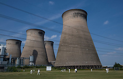 © Licensed to London News Pictures. 19/05/2018. Ferrybridge, UK.  Ferrybridge Power Station Cricket Club play their match against Horbury Bridge Cricket Club underneath the disused cooling towers of the power station at Ferrybridge, Yorkshire, UK.  Photo credit: Anna Gowthorpe/LNP
