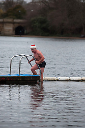 © Licensed to London News Pictures. 25/12/2011. LONDON, UK. A swimmer with a festive hat takes a quick dip in the Serpentine in London ahead of a Christmas Race taking place there today (25/12/2011). Members of the Serpentine Swimming Club today carried out their Christmas Day Swim, the race, known as the Peter Pan Cup after former patron and author JM Barrie, is a tradition dating back to 1864. Photo credit: Matt Cetti-Roberts/LNP
