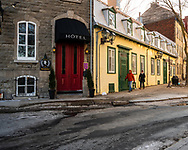 Quebec City, Quebec, Canada -- November 30, 2019.  Two pedestrians walk past a boutique hotel on a side street in Quebec City, Canada.