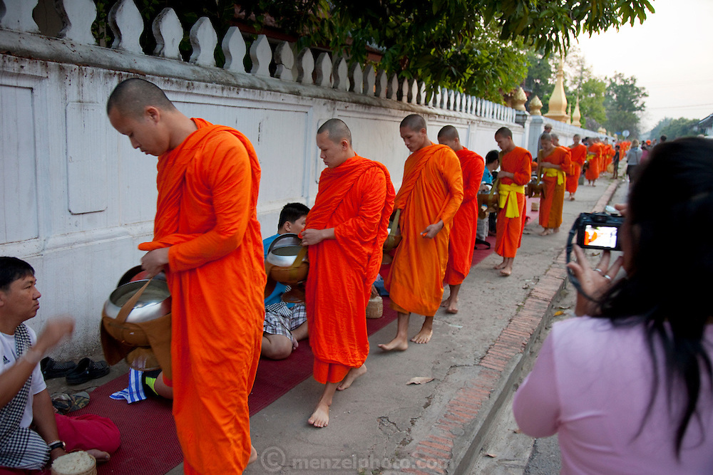 Every morning at dawn, Buddhist monks walk down the streets collecting food alms from devout, kneeling Buddhists, and some tourists. They then return to their temples (also known as wats) and eat together. This procession is called Tak Bat, or Making Merit.