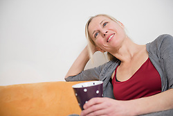 Mature woman relaxing on couch with cup, smiling
