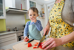 Son nibbling vegetables while mother is cutting them