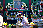 Ashgabat, Turkmenistan, October 1997..A street trader at an Independence Day carnival with a portrait of President Saparmurat Niyazov on his stall. Poverty-stricken, but rich in oil and gas resources, this Central Asian former Soviet republic is ruled by the autocratic President Saparmurat Niyazov, or Turkmenbashi as he has renamed himself...............