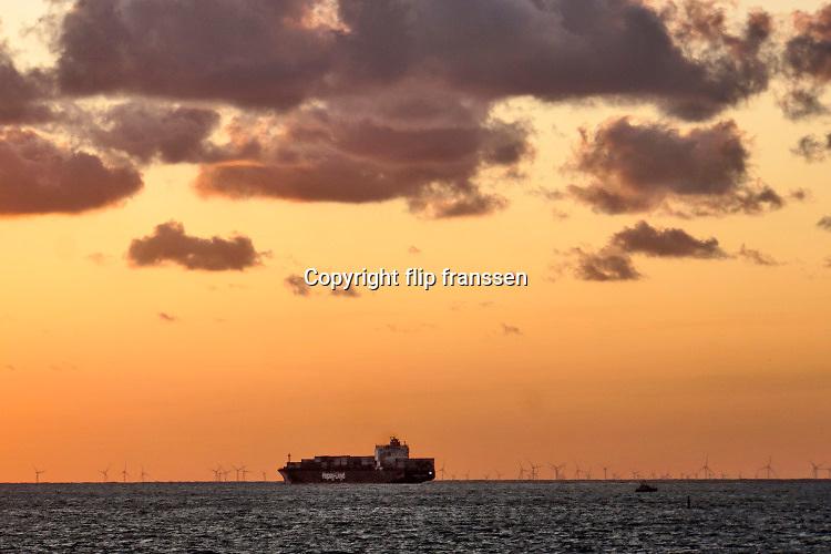 Nederland, Breskens, 5-9-2019 Een containerschip vaart op de Westerschelde vanuit de haven van Antwerpen richting volle zee. Tegen de ondergaande zon, zonsondergang .. Foto: Flip Franssen