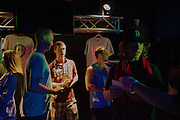 TRUSSVILLE, AL - AUGUST 27, 2013: Bailey Little, 27, (left), Ryan Kendrick, 24, Jeremy Reyer, 26, and Baylen Clough, 26, (right) stand near the merchandise table after a service at The Basement, a Christian youth ministry in Alabama. The service was the first to be held since the ministry's founder Matt Pitt was arrested for impersonating a police officer on August 20, 2013. CREDIT: Bob Miller for The New York Times.