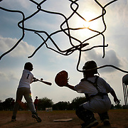 Alan Guerra, 11, swings at a pitch as Edgar Alfaro, 12, puts his catchers mitt out during batting practice for their 11 to 12 year-old little league team a practice field at Municipal Park in McAllen. <br /> Nathan Lambrecht/The Monitor