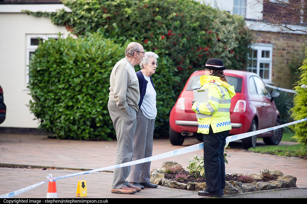 © Licensed to London News Pictures. 27/11/2014. Fetcham, UK. A police officer speaks to the couples elderly neighbours.  A manhunt is under way across two counties after a man and woman were found stabbed to death in Surrey. The bodies were found at a house in Fetcham, near Leatherhead, after Surrey Police were alerted in the early hours.. Photo credit : Stephen Simpson/LNP