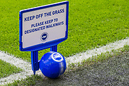 'Keep off the grass' signage and football on the pitch ahead of the Premier League match between Brighton and Hove Albion and Crystal Palace at the American Express Community Stadium, Brighton and Hove, England on 29 February 2020.