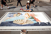 Street artist in Trafalgar Square re-creates the Birth of Venus by Botticelli in chalk and pastels on the pavement near the National Gallery. Some coins are collected in her hat.