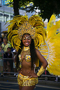A young dancer shows of her yellow feathers with a smile  in East London, United Kingdom,Sept 11 2016. The annual Hackney Carnival took place on a hot summers day and the procession of dancers dressed in various outfits moved through the streets to much joy of the many bystanders.