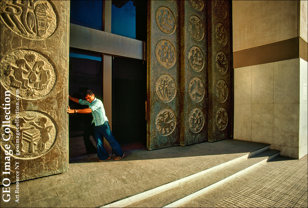 A worker at HSBC Bank Middle East Limited in Bahrain opens the bank's massive bronze doors, which  are  illustrated with the seals of the ancient Dilmun civilization.  HSBC Bank Middle East Limited is the largest and most widely represented international bank in the Middle East, banking authorities say.