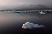 Icebergs from the Jökulsárlón glacial lake pour into the sea before washing up on the black volcanic sandy beach, in South-East Iceland. The skies cleared for dusk.