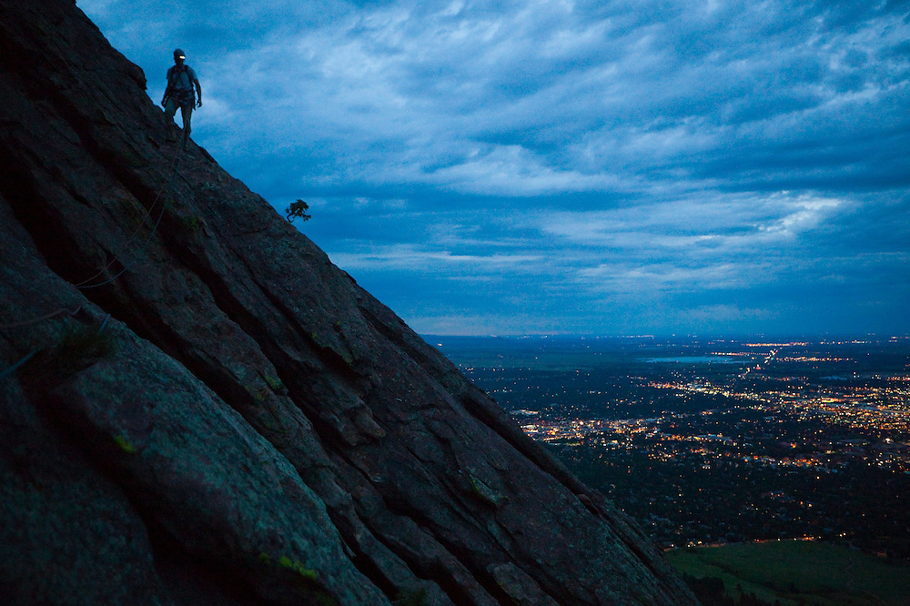 Obadiah Reid climbs the First Flatiron at night above Boulder, Colorado.