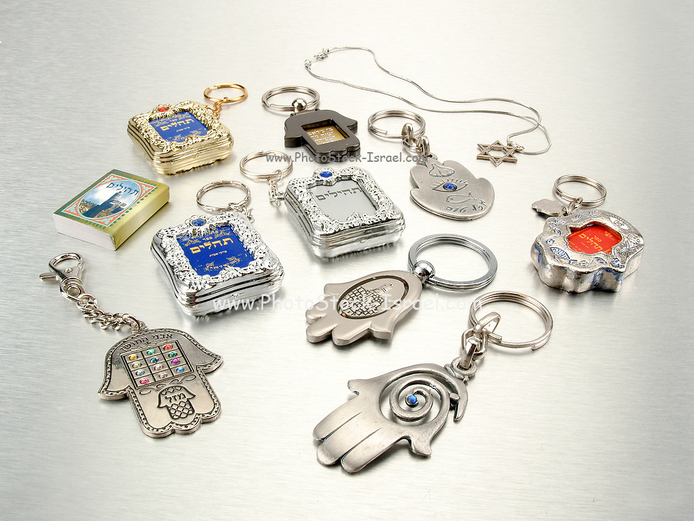 Small Judaica symbols, Humsa, Magen David, and Tehilim on silver background all popular amulets for protection from the envious or evil eye