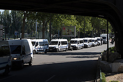 © Licensed to London News Pictures . 09/05/2017. Paris, France . Dozens of police vans at the scene where French police have cleared approximately 1000 people from an ad hoc roadside camp under roadways along a central reservation , in which migrants were living , in Porte de la Chapelle in North Paris , this morning (9th May 2017) . Photo credit: Joel Goodman/LNP