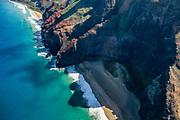 Na Pali Coast sea cliffs above Honopu Beach seen via helicopter over island of Kauai, Hawaii, USA. Kalalau Beach is at upper left.