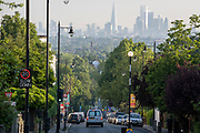 With the London skyline in the far distance, a white van descends the 20mph steep gradient of Gypsy Hill in Crystal Palace, on 16th June 2021, in London, England.