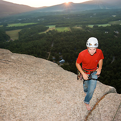 A rock climber on the top of Cathedral Ledge at sunrise.  Echo Lake State Park in North Conway, New Hampshire.  White Mountains.