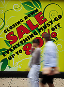 Sale signs in shop windows offer Sale reductions, large % off retail goods on Oxford Street in Central London. This is a busy shopping area full of all the main high street chain stores.