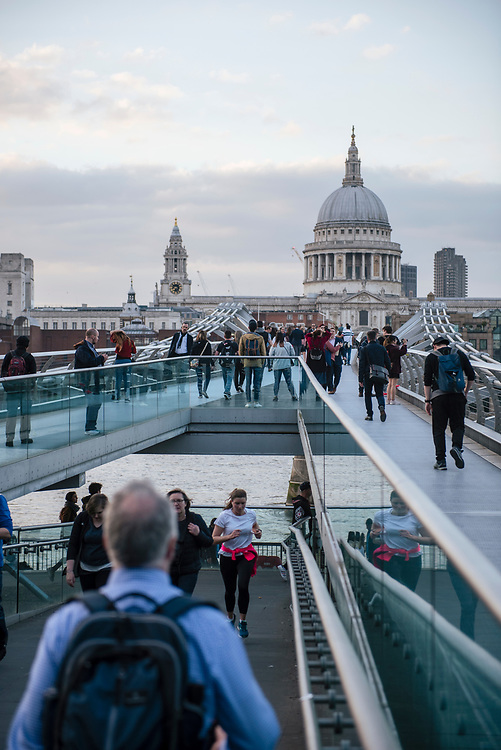 London, England - May 4, 2018: At sunset pedestrians cross the Thames River on the Millennium Bridge, built in 2002. St. Paul's Cathedral is in the background.