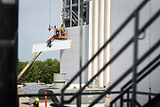 Construction workers place an exterior panel at the Puris pea protein processing facility in Dawson, Minnesota, on Tuesday, June 8, 2021.