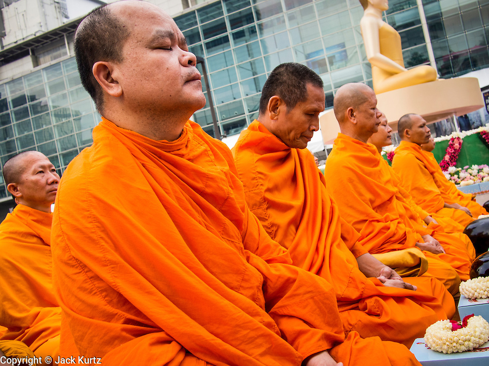 08 SEPTEMBER 2013 - BANGKOK, THAILAND: Buddhist monks pray next to a statue of the Buddha before a mass alms giving ceremony in Bangkok. 10,000 Buddhist monks participated in a mass alms giving ceremony on Rajadamri Road in front of Central World shopping mall in Bangkok. The alms giving was to benefit disaster victims in Thailand and assist Buddhist temples in the insurgency wracked southern provinces of Thailand.      PHOTO BY JACK KURTZ
