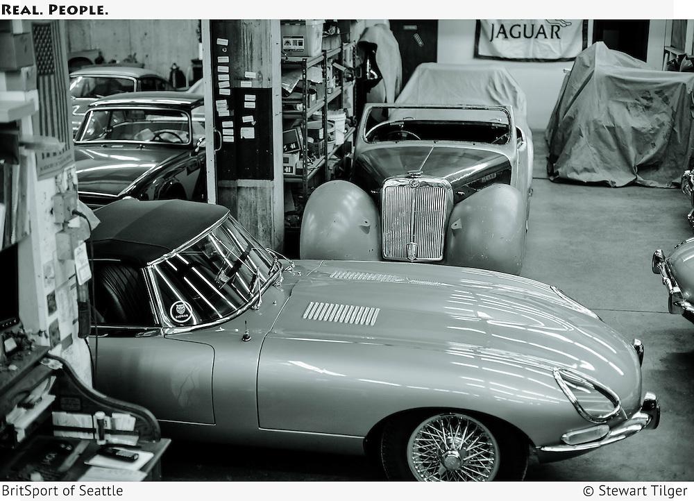 BritSport shop floor. 1967 Jaguar E Type in foreground. Triumph 1800 Roadster in background.