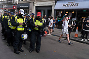 Hours before the England football team play an historic game against Italy the first time since 1966 that the English national team have played in a major mens international football final, police officers prepare to engage with thousands of mainly young supporters without face coverings nor social distancing outside Leicester Square tube station, on 11th July 2021, in London, England.