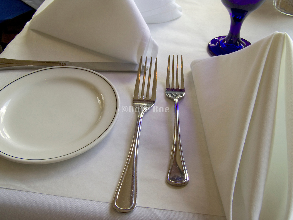 dinner table set with plates glasses and utensils