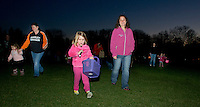 Maia Heller followed by her mom Katie Heller begins her search at Laconia Parks and Recreation's flashlight Easter Egg Hunt Saturday evening at Smith Track.  (Karen Bobotas/for the Laconia Daily Sun)