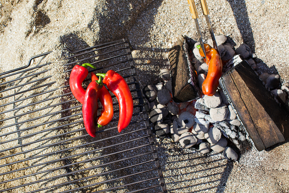Red peppers being barbecued over a fire on the sandy beach of the Minquiers - alfresco dining in a tropical paradise in Jersey, CI