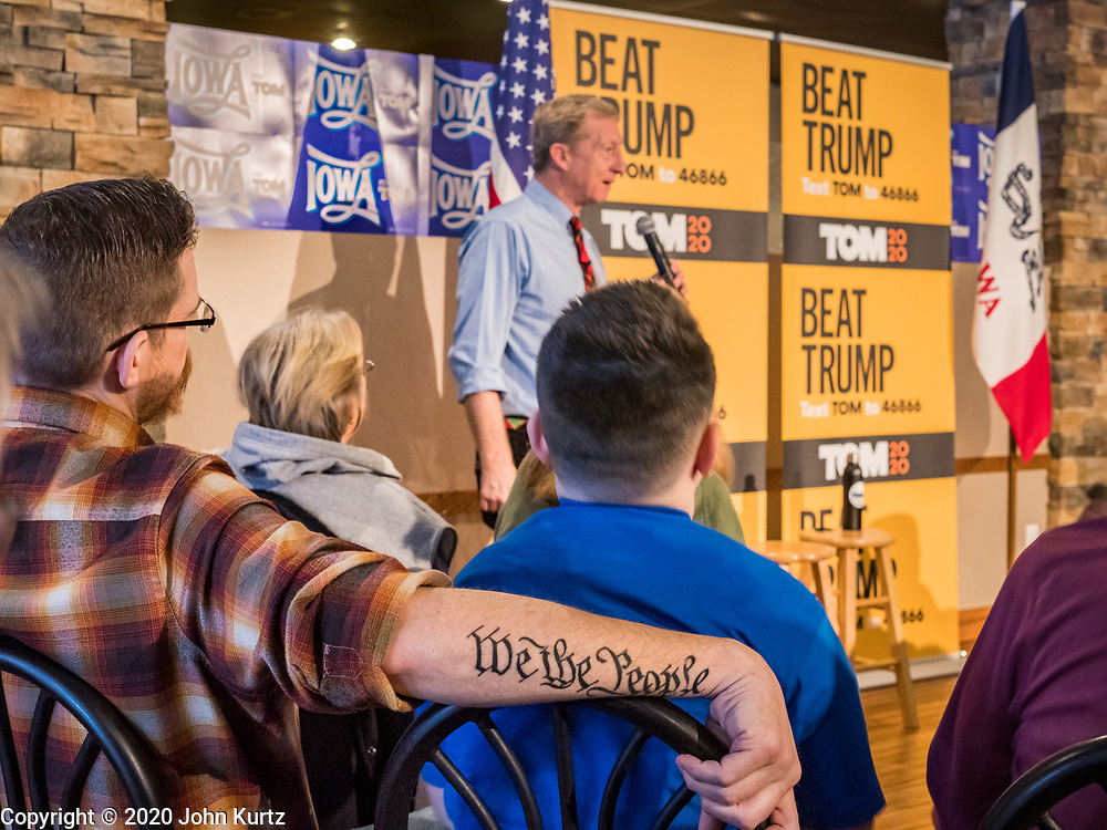 "29 JANUARY 2020 - KNOXVILLE, IOWA: A man, who identified himself as a Libertarian, with ""We The People,"" from the US Constitution tattooed on his arm, listens to TOM STEYER at a campaign event in Knoxville, about 40 miles southeast of Des Moines, Wednesday. About 60 people attended the campaign meet and greet. Steyer, a California businessman, is campaigning to be the Democratic nominee for the US Presidency in 2020. Iowa holds the first selection event of the 2020 election cycle. The Iowa Caucuses are Feb. 3, 2020.        PHOTO BY JACK KURTZ"
