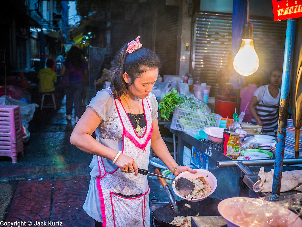 29 DECEMBER 2012 - BANGKOK, THAILAND:  A woman makes dinner for customers at her street food stall in the Chinatown area of Bangkok, Thailand.       PHOTO BY JACK KURTZ