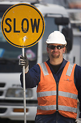 """Bilfinger Safety Man in front of his truck with """"Slow"""" sign"""