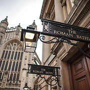 The entrance to the historic Roman Baths that give the city of Bath, Somerset, its name. In the background, at left, is the tower of Bath Abbey.
