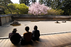 Visitors looking at famous dry raked gravel garden at Ryoanji in historic Kyoto Japan