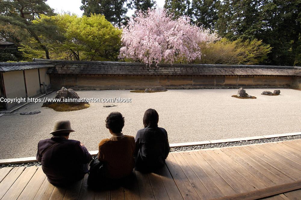 Visitors looking at famous dry raked gravel garden at Ryoanji in historic Kyoto Japan