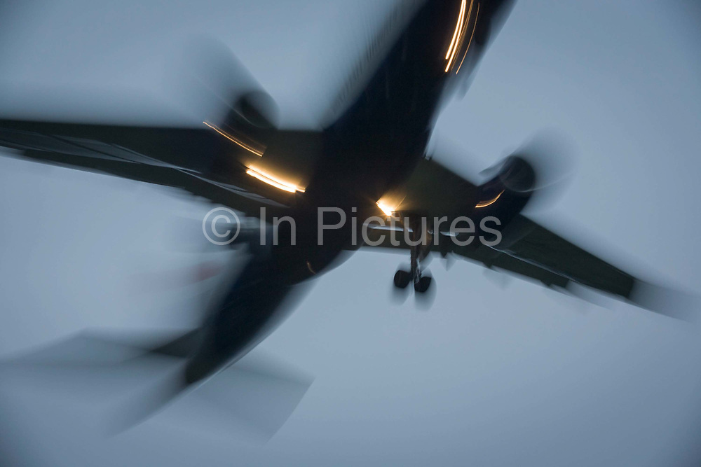 With bright landing lights on, blurred jet airliner lands at London Heathrow airport. As the plane passes overhead, we see its blurred shape against a darkening sky at dusk - a busy time in the airport's day. London Heathrow is a major international airport, the busiest airport in the United Kingdom and the busiest airport in Europe by passenger traffic. It is also the third busiest airport in the world by total passenger traffic, handling more international passengers than any other airport around the globe. From the chapter entitled 'Up in the Air' and from the book 'Risk Wise: Nine Everyday Adventures' by Polly Morland (Allianz, The School of Life, Profile Books, 2015).