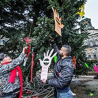 """Nederland, Amsterdam, 8 januari 2017.<br />Kunstenares Godelieve Smulders hangt kunstwerkjes met een boodschap in de vorm van handjes in de kerstboom op de Dam  en betrekt omstanders erbij om hetzelfde te doen zoals Furkan Yildrim (zie foto)<br />Een handje dat """"stop"""" zegt.<br />Met dit nieuwe symbool gaat Godelieve Smulders over de hele wereld het kwaad van verkrachting te lijf om te beginnen op de Dam.<br /><br /><br /><br />Foto: Jean-Pierre Jans"""
