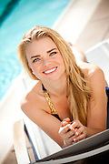 Smiling Blonde Lady Relaxing By The Pool