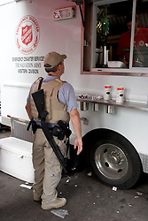 10 Sept 2005.  New Orleans, Louisiana. Hurricane Katrina aftermath.<br /> A member of the security services waits for hot food served from the Salvation Army truck parked on Canal Street.<br /> Photo; ©Charlie Varley/varleypix.com