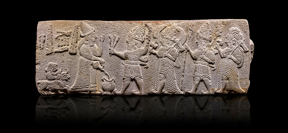 Aslantepe Hittite relief sculpted orthostat stone panel. Limestone, Aslantepe, Malatya, 1200-700 B.C. . Anatolian Civilisations Museum, Ankara, Turkey<br /> <br /> Scene of the king's offering drink and sacrifice to the gods. King pours from the pitcher to the vessel (libation); behind the king is a servant bringing a sacrifice. Storm God across the king holds Teshup, a triple lightning bundle - sickle, and a spear-mace set in the other orthostat; the goddess Ishtar holds weapon in both. All six figures have shoes with the curled ends. <br /> <br /> Against a black background. <br /> <br /> If you prefer to buy from our ALAMY STOCK LIBRARY page at https://www.alamy.com/portfolio/paul-williams-funkystock/hittite-art-antiquities.html . Type - Aslantepe - in LOWER SEARCH WITHIN GALLERY box. Refine search by adding background colour, place, museum etc.<br /> <br /> Visit our HITTITE PHOTO COLLECTIONS for more photos to download or buy as wall art prints https://funkystock.photoshelter.com/gallery-collection/The-Hittites-Art-Artefacts-Antiquities-Historic-Sites-Pictures-Images-of/C0000NUBSMhSc3Oo