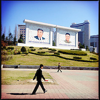 Pedestrians walk past giant paintings of Kim Il-sung and Kim Jong-il in downtown Pyongyang, North Korea.