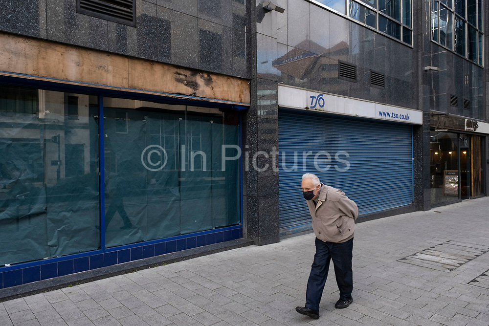 With new local coronavirus lockdown measures now in place and Birmingham currently set at 'Tier 2' or 'high', an elderly man wearing a face mask passes closed down shops in the city centre on 14th October 2020 in Birmingham, United Kingdom. This is the first day of the new three tier system in the UK which has levels: 'medium', which includes the rule of six, 'high', which will cover most areas under current restrictions; and 'very high' for those areas with particularly high case numbers. Meanwhile there have been calls by politicians for a 'circuit breaker' complete lockdown to be announced to help the growing spread of the Covid-19 virus.