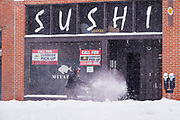 26 JANUARY 2021 - DES MOINES, IOWA: A man clears fresh snow from the sidewalk in front of a restaurant in Des Moines. Workers in Des Moines started cleaning up a record snowfall Tuesday morning. The National Weather Service reports that 10.3 inches of snow fell at Des Moines International Airport Monday, January 25, breaking the daily record of 10 inches for January 25 set in 1895. Many downtown businesses closed for the day because of the snow, since roads throughout central Iowa were snowpacked and hard to drive.        PHOTO BY JACK KURTZ