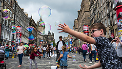 Edinburgh, Scotland, UK; 2 August, 2018. On day before official opening of the Edinburgh Festival Fringe 2018, many tourists enjoying performers including this man making bubbles for children.