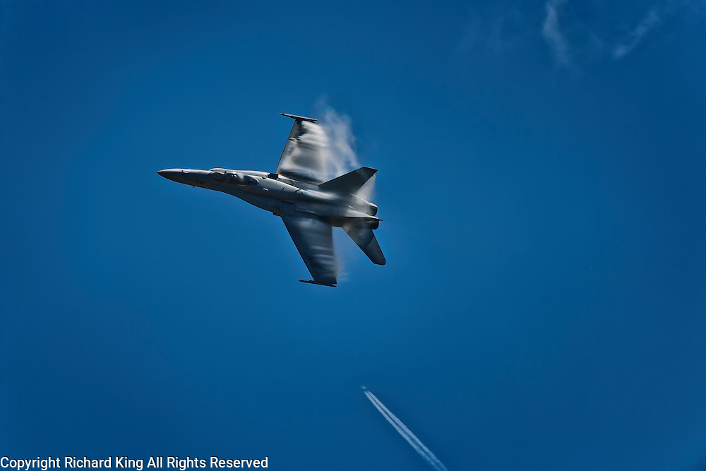 Color photographic image of a U. S. Navy F/A-18 Hornet performing aerobatics and creating wing vapor and a commercial airliner vapor trail in the distance