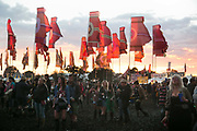 Party people and red banners in the setting sun at Glastonbury Festival 25th July 2016, Somerset, United Kingdom.  The Glastonbury Festival runs over 3 days and has 3000 acts, including music, art and performance and approx. 150.000 attend the anual event.